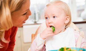 ребенок кушает броколли
